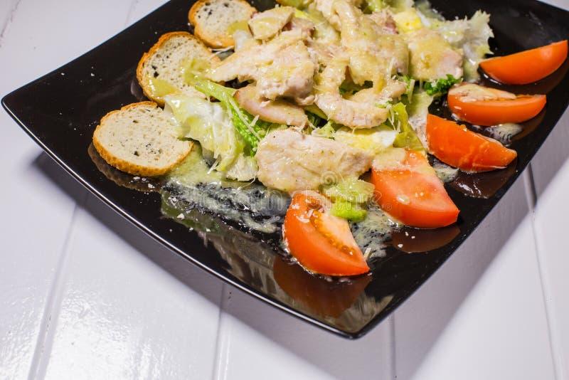 Salade de César avec le plat noir d'oeufs de lard et de caille images stock
