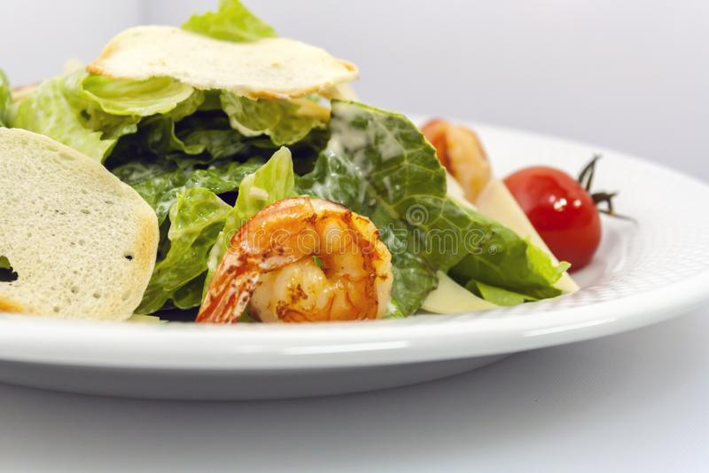 Salade de César avec les croûtons, le fromage, la laitue et les crevettes grillées sur un fond blanc image libre de droits