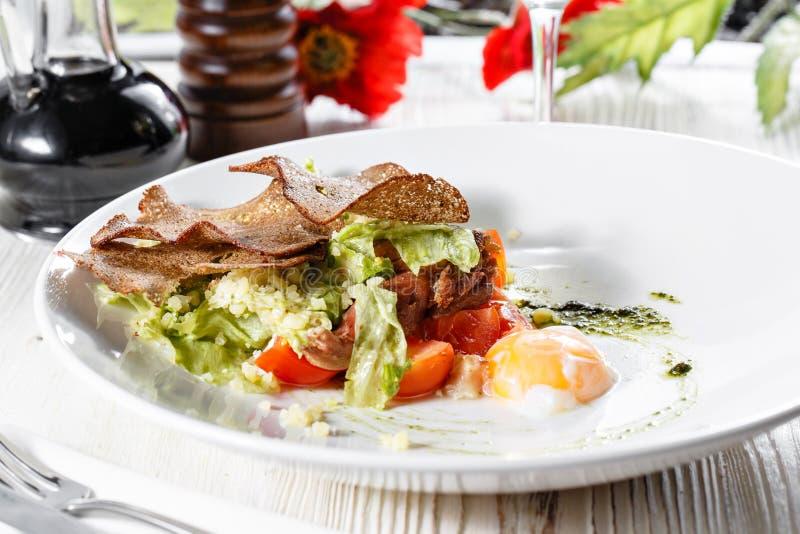 Salade de César classique avec le poulet, l'oeuf poché, les feuilles de laitue, les biscuits, le parmesan et les tomates et la cr images stock
