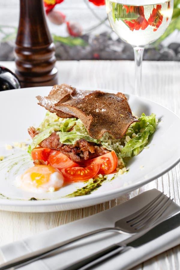 Salade de César classique avec le poulet, l'oeuf poché, les feuilles de laitue, les biscuits, le parmesan et les tomates et la cr photographie stock libre de droits