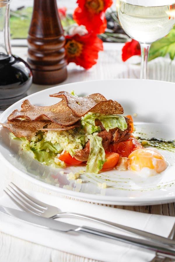 Salade de César classique avec le poulet, l'oeuf poché, les feuilles de laitue, les biscuits, le parmesan et les tomates et la cr photos libres de droits