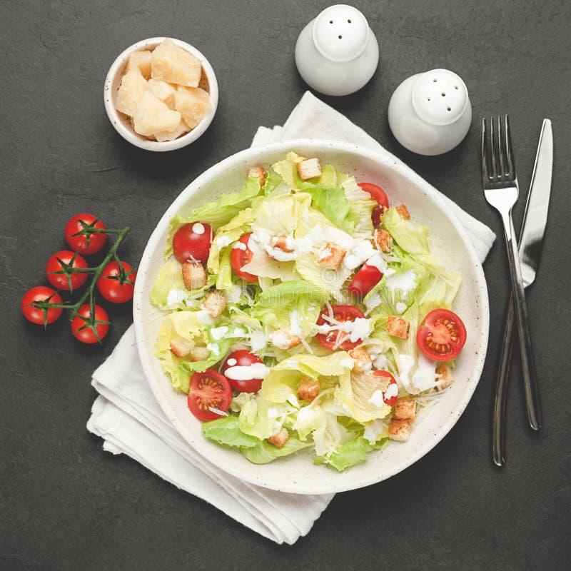 Salade de César du plat blanc au-dessus du fond concret noir photo libre de droits