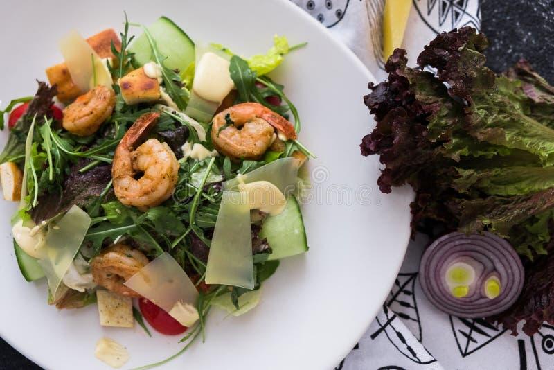 Salade de César fraîche avec des crevettes d'un plat blanc sur le fond en pierre foncé L'appartement s'étendent avec des ingridie photo stock
