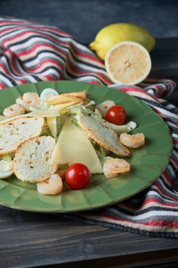 Salade de César fraîche avec des crevettes dans un plat vert sur une table en bois légère photo libre de droits