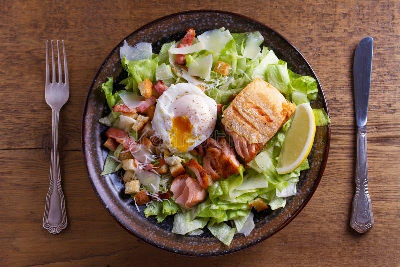 Salade de César saumonée La casserole croustillante a fait frire le filet saumoné, le lard, l'oeuf poché, la laitue et les croûto images stock