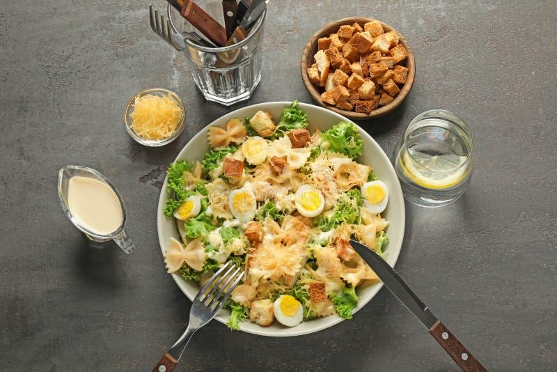 Salade de César savoureuse avec des pâtes dans la cuvette sur la table grise image stock