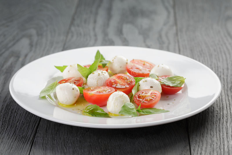 Salade de Caprese avec de mini boules de mozzarella et images stock