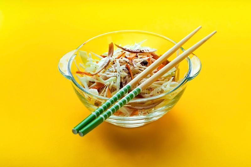 Salade de choux de salade de choux dans le bol en verre avec des baguettes sur le fond jaune, d'isolement, concept d'aliment biol image stock