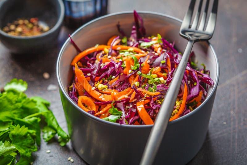 Salade de choux dans une cuvette grise sur le fond foncé Salade de chou rouge et de carotte images libres de droits