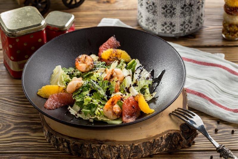 Salade de crevette avec le pamplemousse, l'orange et la laitue coupés en tranches du plat brun sur la table en bois photos libres de droits