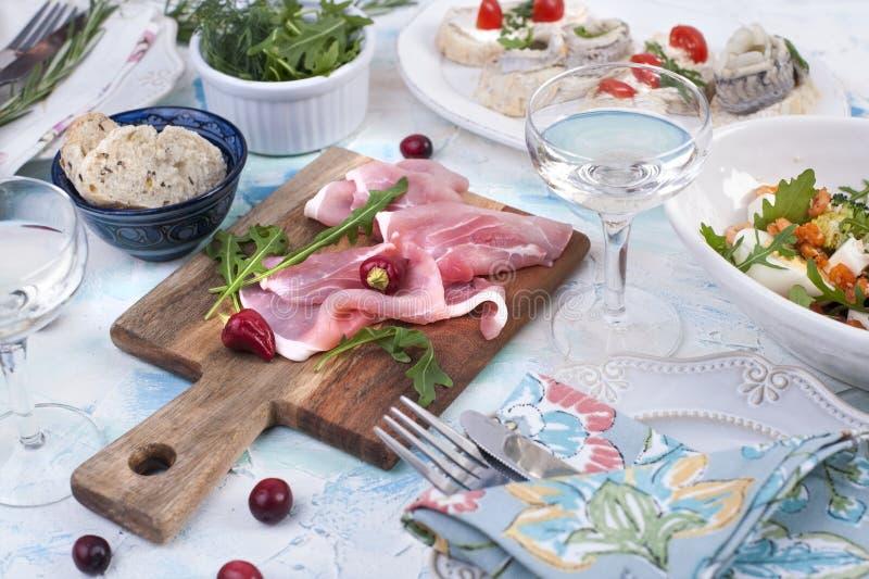 Salade de crevette et de légumes dans un plat blanc et un verre de vin, de viande sur un conseil en bois, et de sandwichs photographie stock