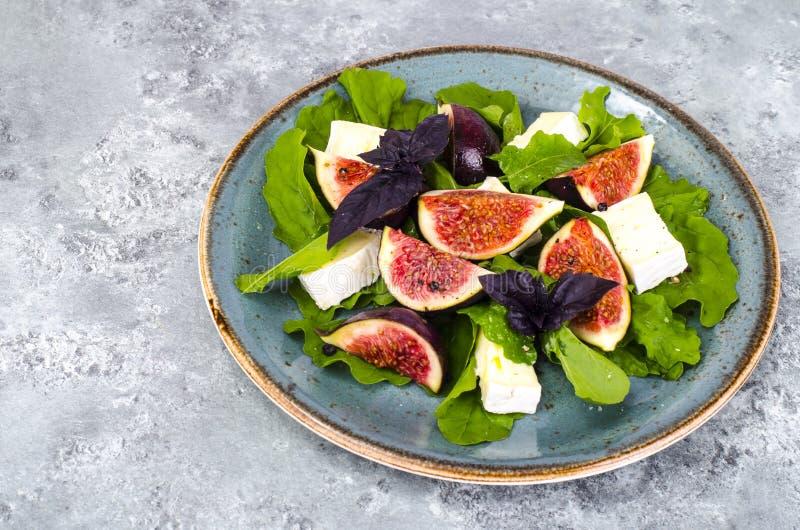 Salade de delicatessen avec figues et fromage sur fond bleu gris images stock
