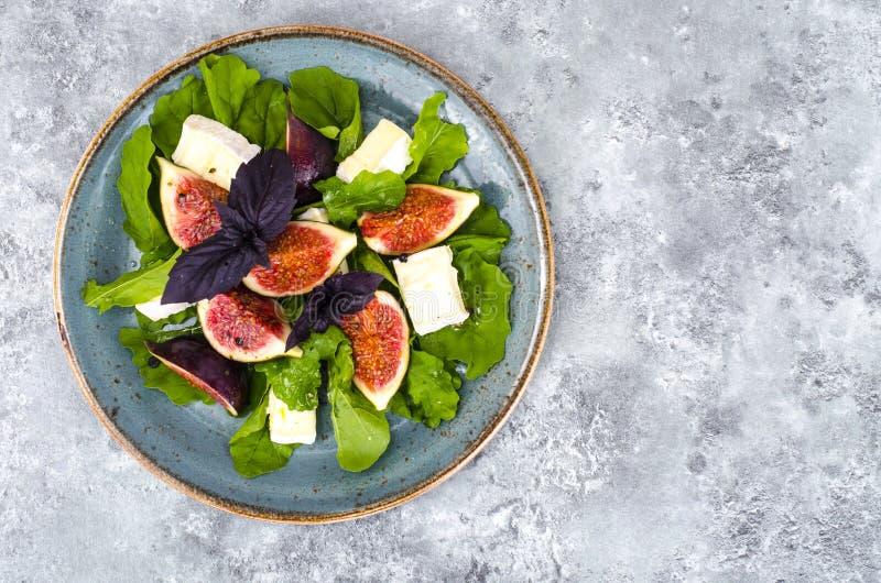 Salade de delicatessen avec figues et fromage sur fond bleu gris image libre de droits