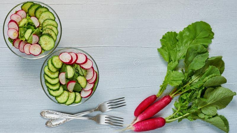 Salade de detox d'été avec le radis, concombre, épinards dans des deux bols en verre sur la table de cuisine grise Petit déjeuner image libre de droits
