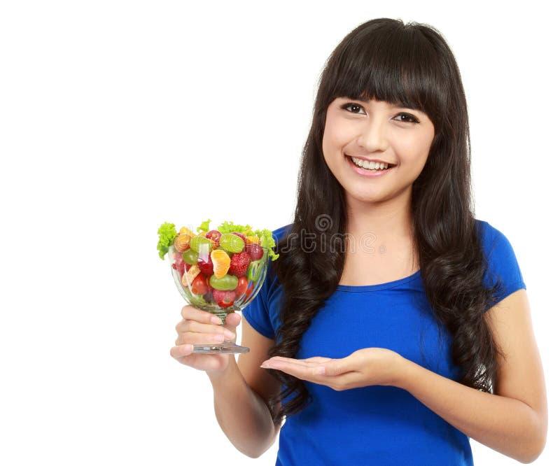 Salade de fruits attrayante de fixation de jeune femme photographie stock