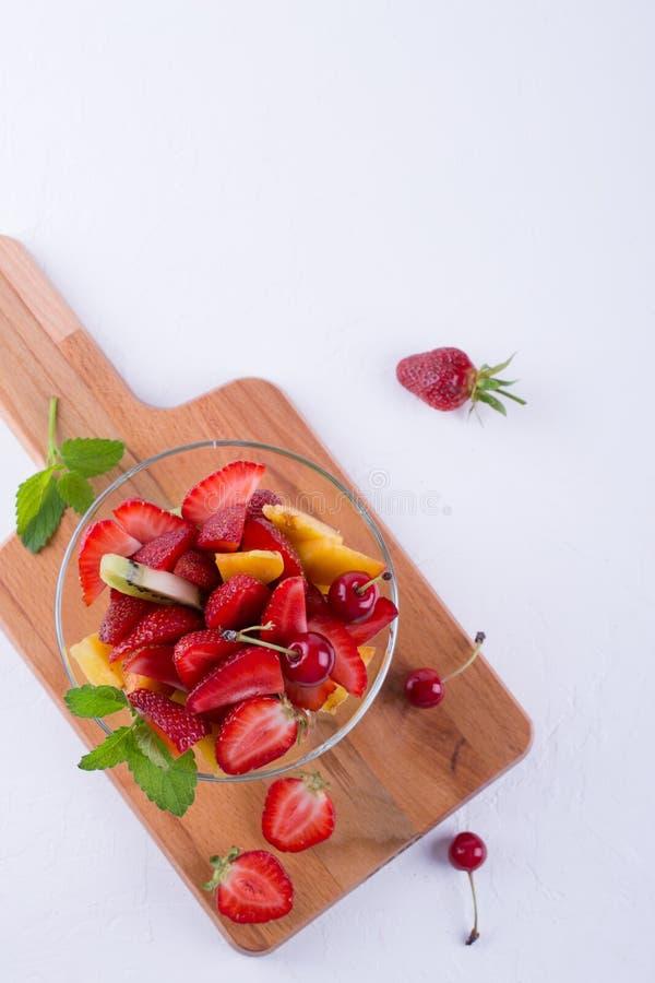 Salade de fruits colorée dans le bol en verre Fraises, kiwis et abricots photo stock