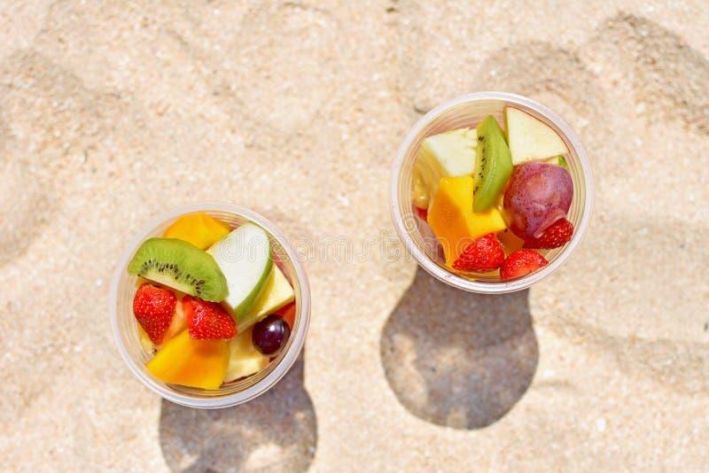 Salade de fruits délicieuse dans la tasse en plastique sur la plage photographie stock