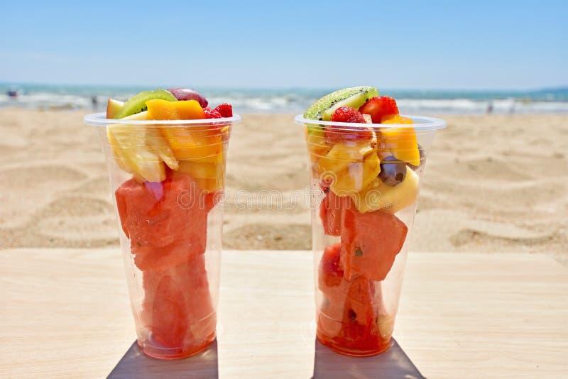 Salade de fruits dans des tasses en plastique à emporter sur la plage photographie stock