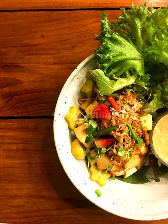 Salade de fruits saine de mélange avec l'écrimage de quinoa et habillage dans le plat blanc photos libres de droits