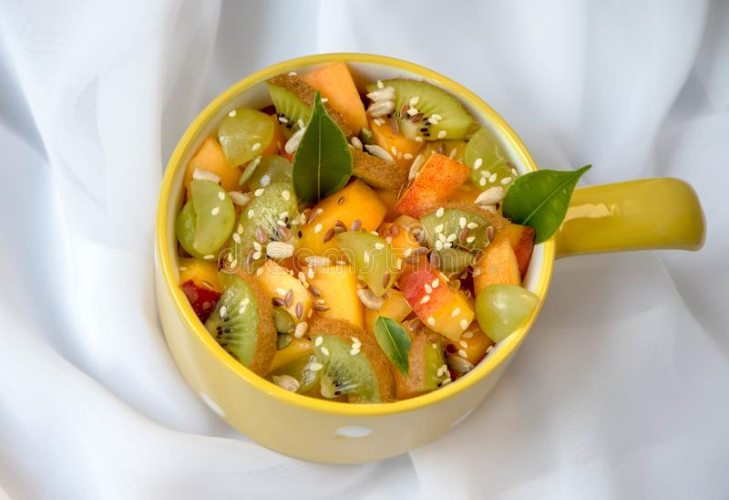 Salade de fruits, sur un fond blanc, avec les feuilles vertes photos libres de droits