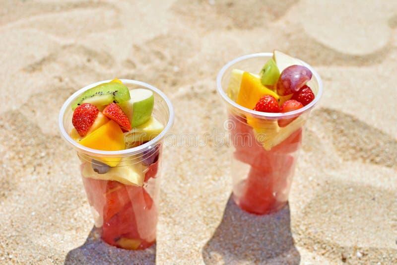 Salade de fruits tropicale dans la tasse à emporter sur la plage photo stock