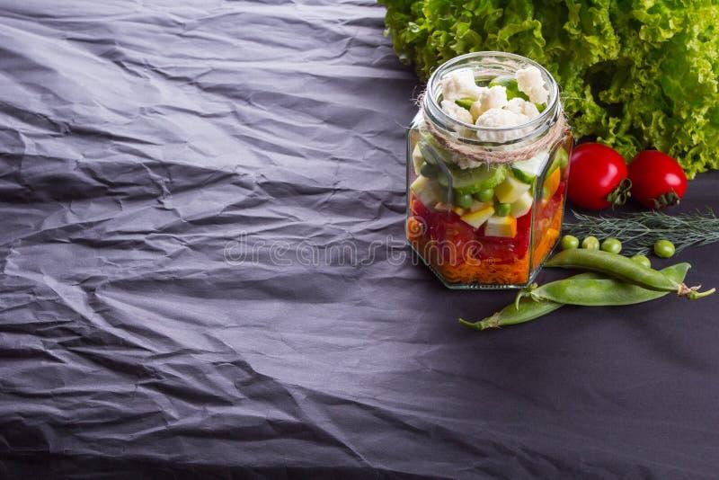 Salade de légume frais avec des verts dans le pot sur un conseil en bois, fond texturisé noir Avec l'espace pour le texte Nourrit images stock