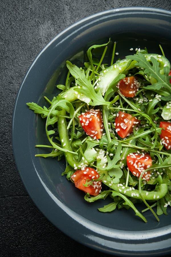 Salade de légume frais des légumes organiques dans un plat sur un fond noir photo stock