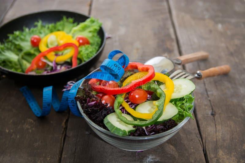 Salade de légumes frais avec la bande de mesure au-dessus du backgroun en bois photo stock