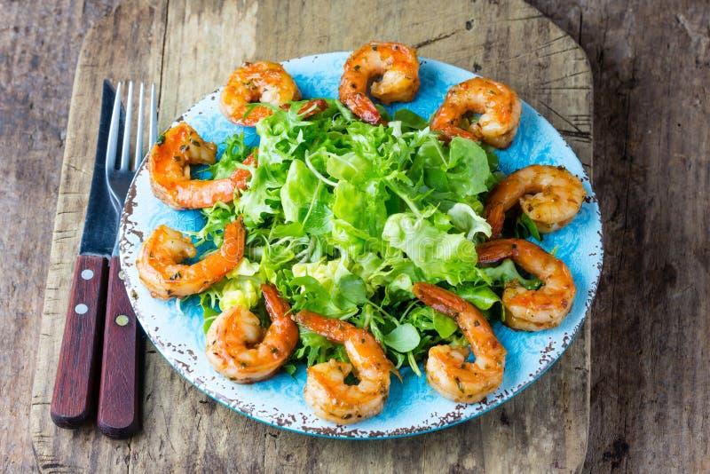 Salade de laitue de Srimp de plat bleu, fond rustique en bois photographie stock