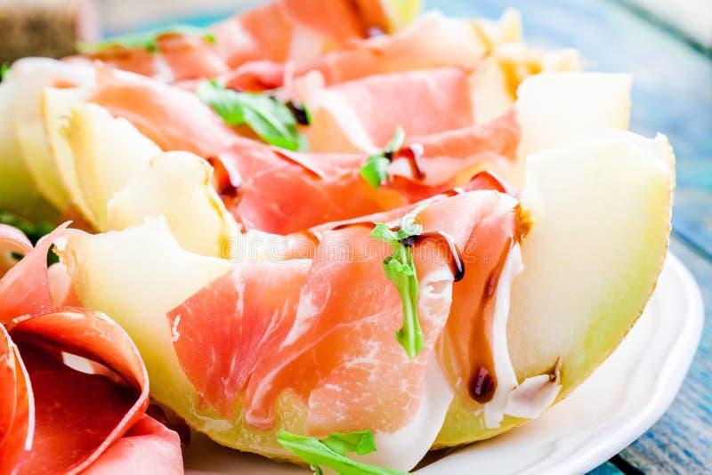 Salade de melon avec les tranches minces de prosciutto, de feuilles d'arugula et de plan rapproché balsamique de sauce photo libre de droits