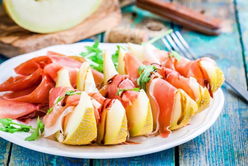 Salade de melon avec les tranches minces de prosciutto, de feuilles d'arugula et de sauce balsamique photographie stock libre de droits