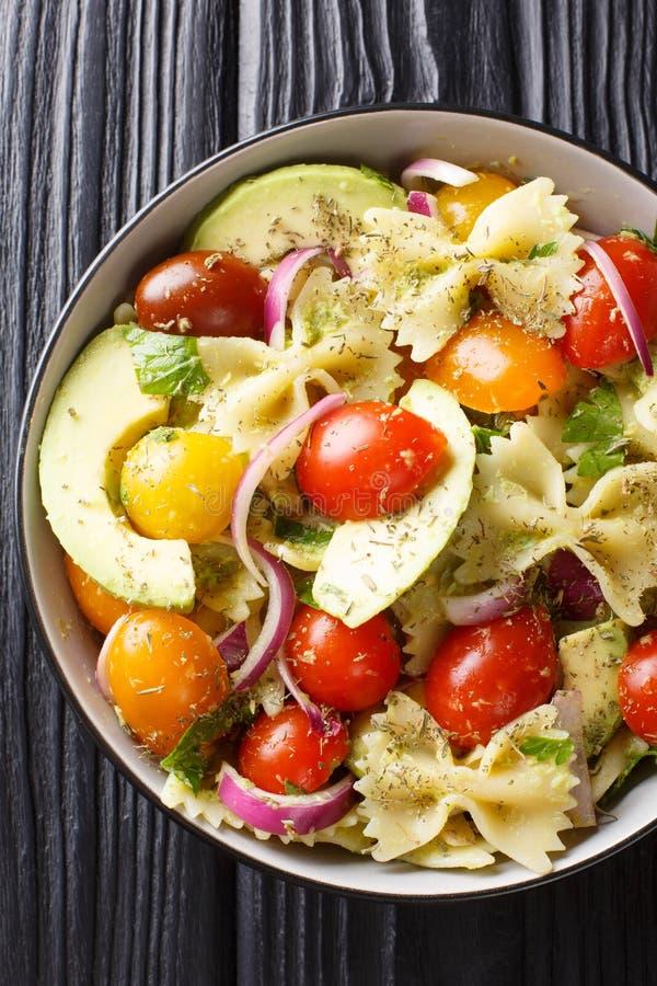 Salade de pâtes de Farfalle d'apéritif avec le plan rapproché mûr d'avocat, d'oignon et de tomate dans une cuvette Vue sup?rieure photographie stock