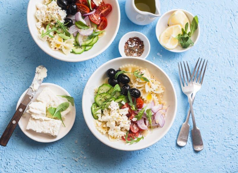 Salade de pâtes méditerranéenne Farfalle de pâtes, tomates, concombres, olives, feta et salade d'arugula Sur un fond bleu, dessus photographie stock libre de droits