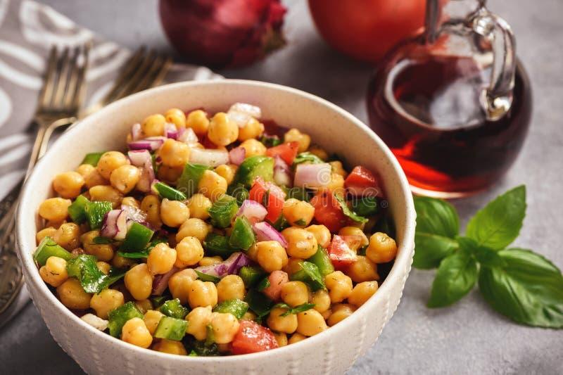 Salade de pois chiche avec le poivron vert, l'oignon rouge et la sauce à vinaigrette image stock