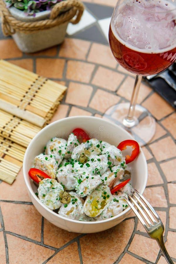 Salade de pomme de terre aux oignons de poivron rouge et de ressort, un verre de vin images libres de droits