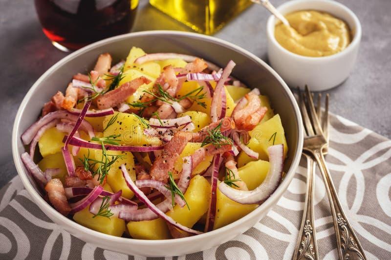 Salade de pomme de terre avec le lard, l'oignon rouge et la sauce à moutarde images stock