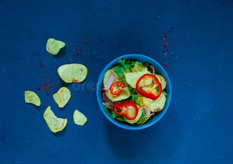 Salade de pomme de terre avec le lard, richement assaisonné avec les épices choisies dans une cuvette bleue sur le fond bleu du b photos libres de droits