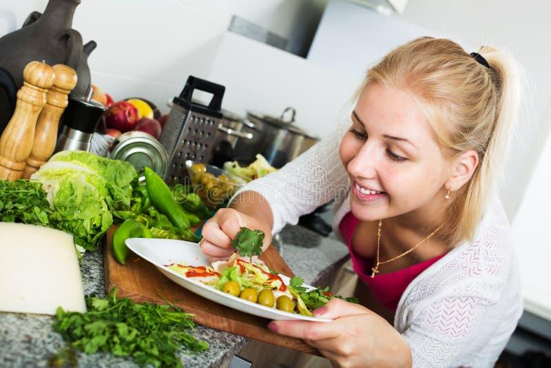 Salade de portion de femme sur la cuisine image stock