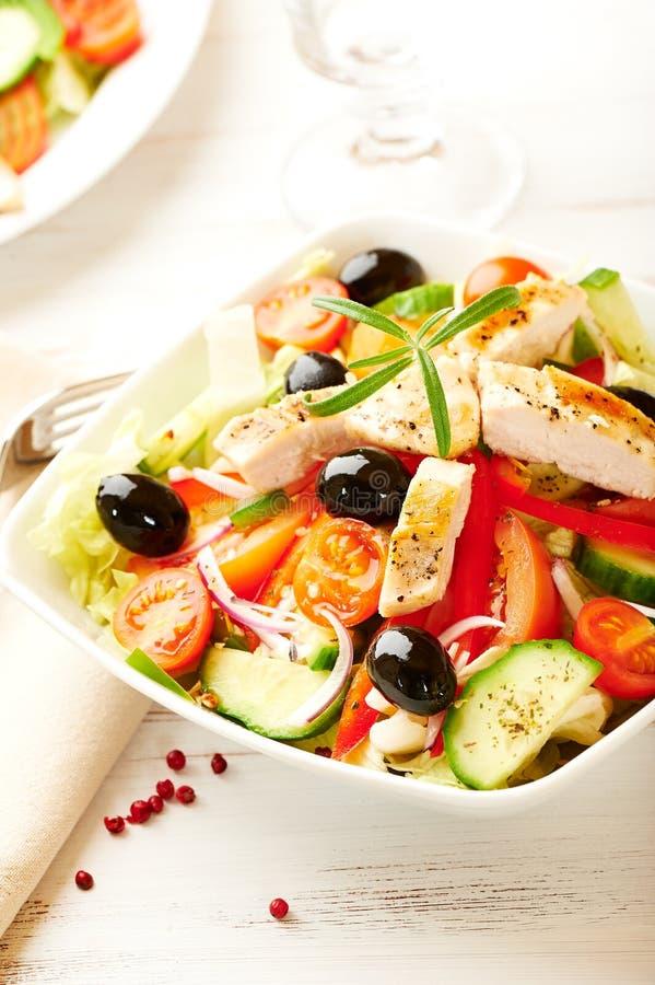 Salade de poulet avec des tomates-cerises, des olives noires, le concombre, l'oignon rouge, le poivron rouge, la laitue et le rom photos libres de droits