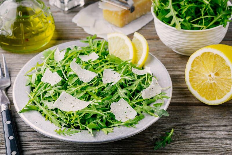 Salade de Rocket avec le parmesan, le citron, l'huile d'olive et les assaisonnements images libres de droits