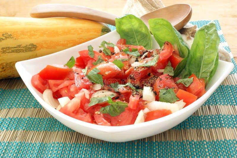 salade de tomate dans la cuvette à l'oignon et au basilic photos stock
