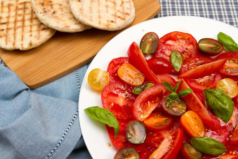 Salade de tomatoe d'héritage avec des pains plats images libres de droits