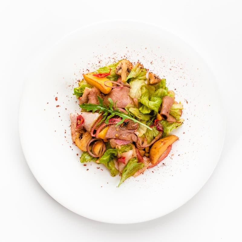 Salade de viande avec du boeuf de rôti, champignons, pommes de terre, oignons, mélange de salade, épices, d'isolement sur le fond photos libres de droits