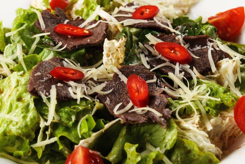 Salade de viande avec du fromage, des herbes et des tomates dans un plat sur un plan rapproché blanc d'isolement de fond photos libres de droits