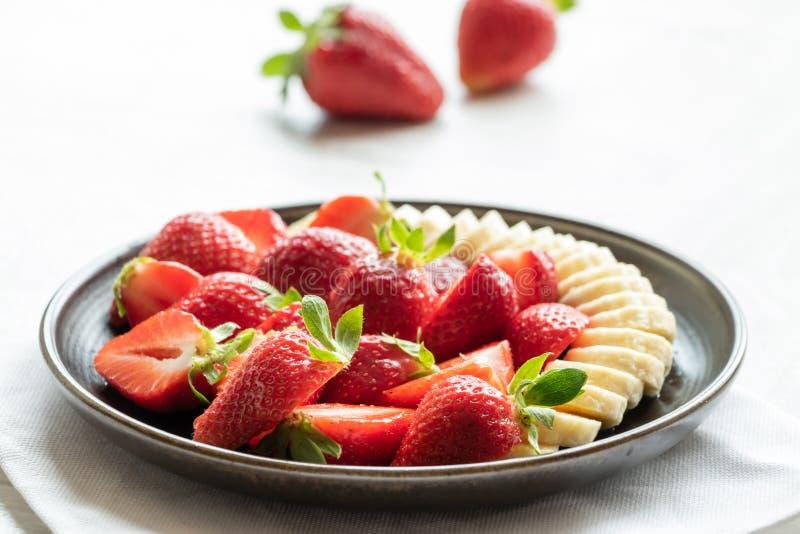 Salade des fraises et de la banane d'un plat fonc? sur un fond clair images stock