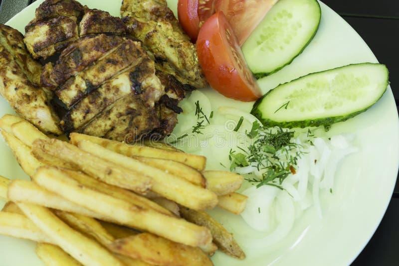 Salade des légumes, viande grillée d'un plat blanc sur un fond noir, menu de photo photos libres de droits