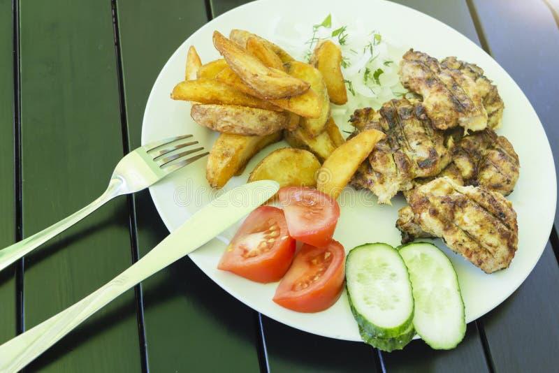 Salade des légumes, viande grillée d'un plat blanc sur un fond noir, menu de photo photographie stock libre de droits