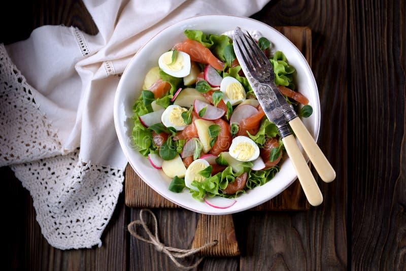 Salade des saumons légèrement salés, des pommes vapeur, des oeufs de caille avec le concombre et du radis photographie stock libre de droits