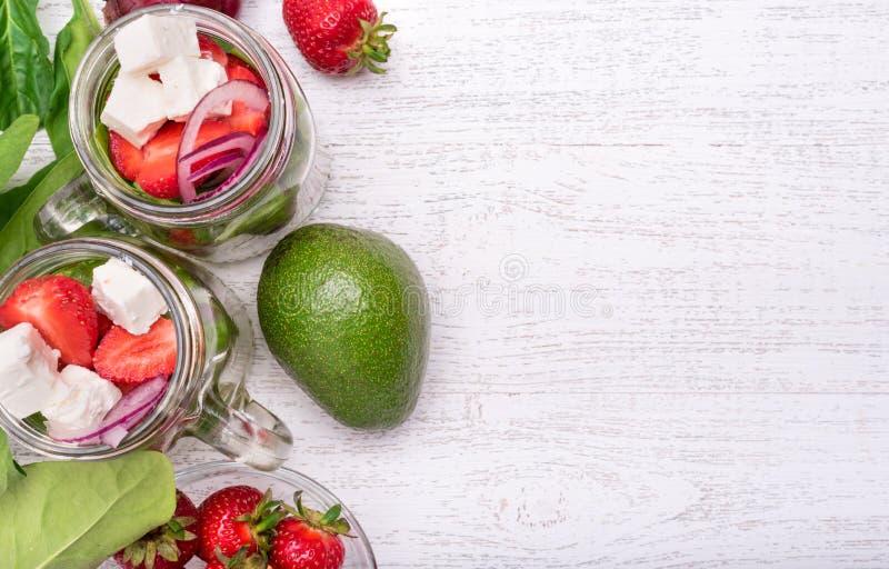 Salade faite maison avec les épinards, la fraise et le fromage dans le pot en verre image stock
