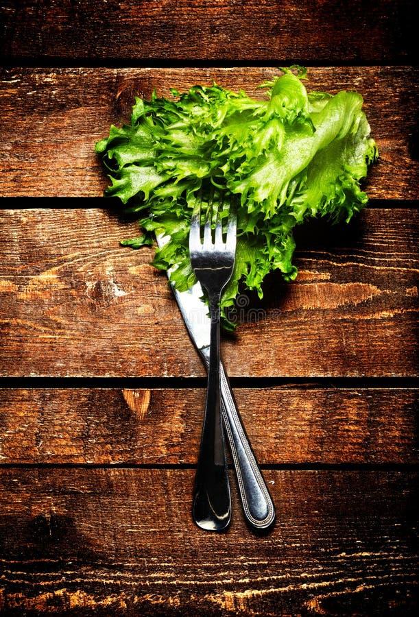Salade fraîche au-dessus de table en bois avec le couteau et la fourchette Nourriture de régime images stock
